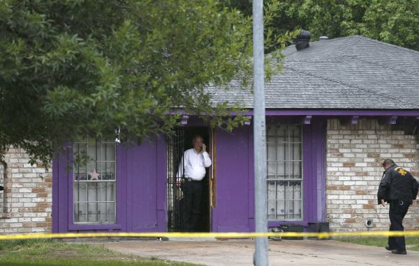 Photo credit: AP | Authorities investigate a home in Houston where police say four homeless men were found in deplorable conditions. Officers who responded to a call expressing concern said said they found three men locked in a garage and a fourth in the home who were malnourished and may have been being held so a captor could cash checks the men were receiving. One person was taken into custody. (July 19, 2013)