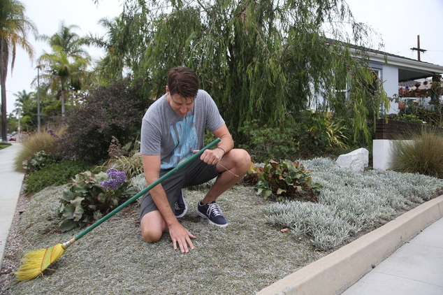 In this Aug. 8, 2014 photo Rick Blankenship holds a photo of his previous grass lawn at his home in Long Beach, Calif. As Californians face a historic drought, more people are tearing out thirsty grass lawns to cut down on water use. (AP Photo/Nick Ut) (THE ASSOCIATED PRESS)