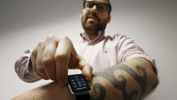 Reuters journalist Matt Siegel inputs his passcode onto his Apple Watch, as his tattoos prevent the device's sensors from correctly detecting his skin. (Jason Reed/Reuters)
