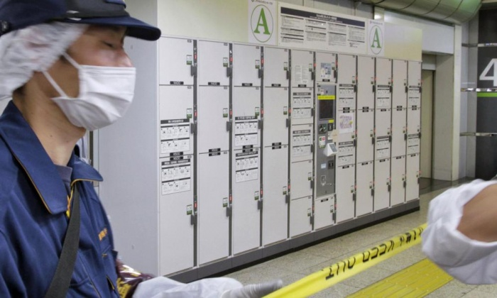 Police guard a baggage locker where a suitcase containing the body of an elderly woman was found at Tokyo station. Photograph: AP