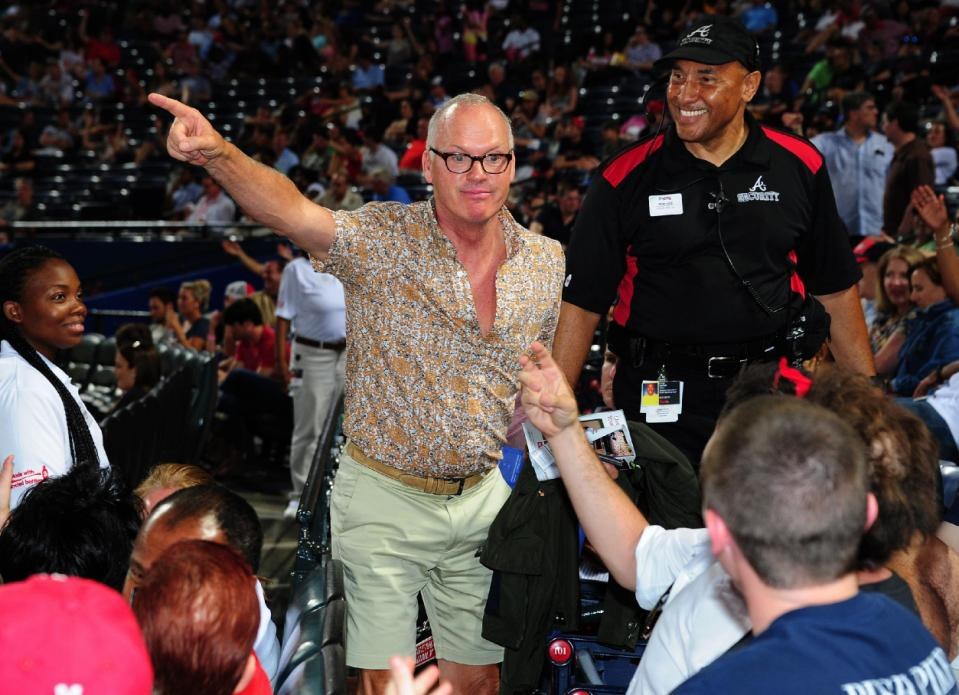 Actor and noted Pittsburgh Pirates fan Michael Keaton playfully points to the scoreboard to a fan of the Atlanta Braves. (Getty Images)