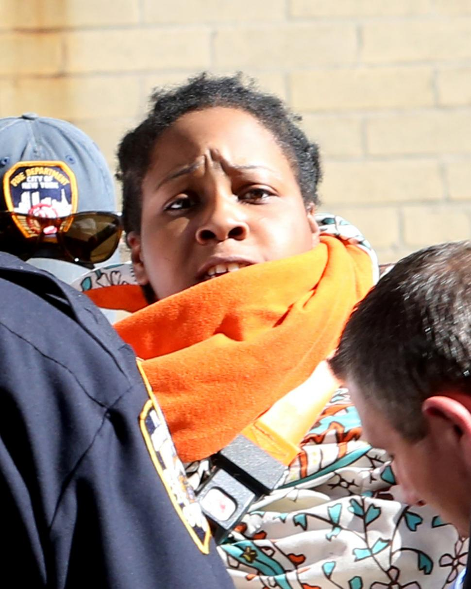 enisha Fearon is taken into an ambulance Thursday after she's accused of throwing her baby out of a window in the Bronx.