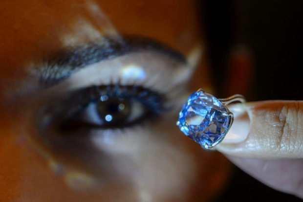 A Sotheby's employee displays the rare Blue Moon Diamond during a preview at Sotheby's, in Geneva, Switzerland. The 12.03 carat blue diamond is the largest cushion-shaped fancy vivid blue diamond ever to appear at auction. (Martial Trezzini/Associated Press)