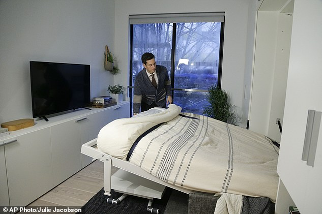 """In this Dec. 22, 2015 photo, Stage 3 Properties co-founder Christopher Bledsoe demonstrates a retractable bed that turns into a sofa when stored inside one of the apartment units at the Carmel Place building in New York. As the city-sponsored """"micro-apartment"""" project nears completion, it's setting an example for tiny dwellings that the nation's biggest city sees as an aid to easing its affordable housing crunch. (AP Photo/Julie Jacobson)"""