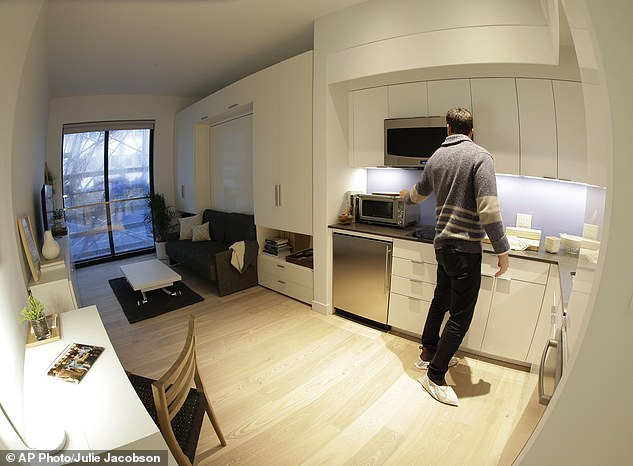 """In this Dec. 22, 2015, photo, Stage 3 Properties co-founder Christopher Bledsoe talks about the kitchen appliances that come with one of the apartment units at the Carmel Place building in New York. As the city-sponsored """"micro-apartment"""" project nears completion, it's setting an example for tiny dwellings that the nation's biggest city sees as an aid to easing its affordable housing crunch. (AP Photo/Julie Jacobson)"""