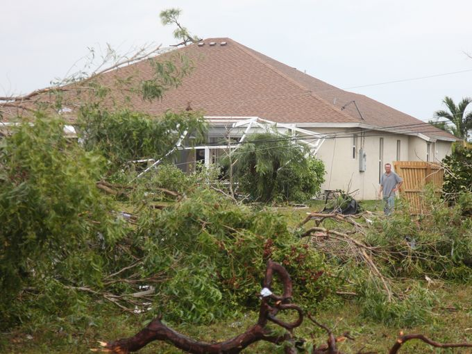 Cape Coral residents assess the damage to homes on Southwest 15th Avenue on Sunday morning. Jack HardmanThe News-Press