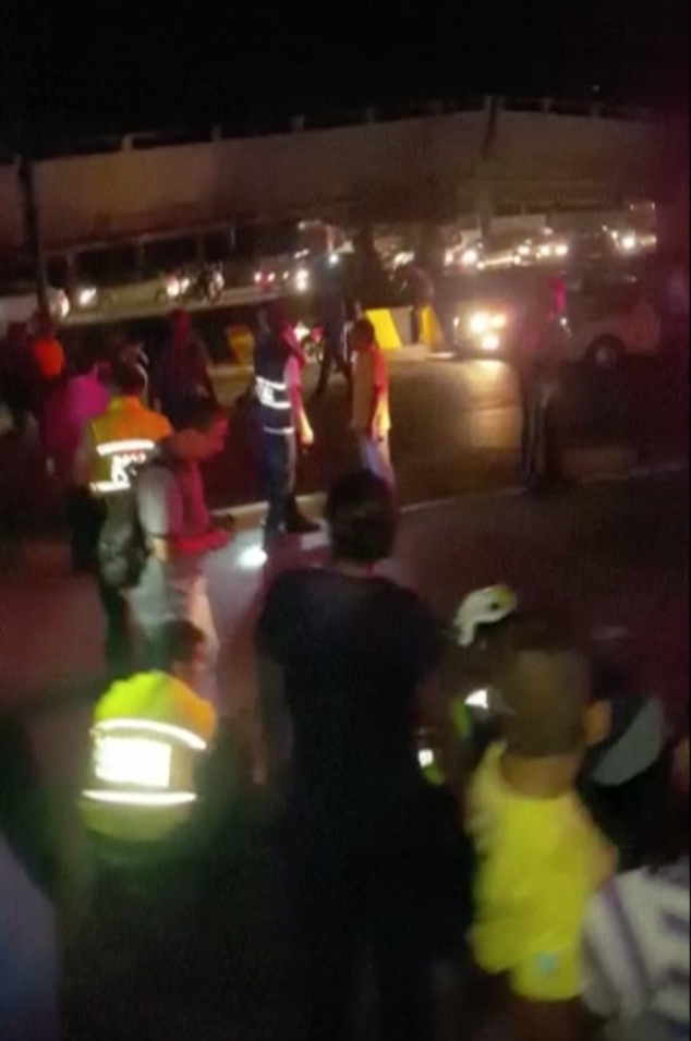 In this image made from a video, people look on after an overpass buckled in Guayaquil, Ecuador, Saturday, April 16, 2016. A powerful, 7.8-magnitude earthquake shook Ecuador's central coast on Saturday, killing dozens of people and spreading panic hundreds of kilometers (miles) away as it collapsed homes and buckled a major overpass. (APTN via AP)