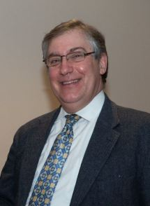 Photo of smiling Jason Bram, wearing suit and tie and eye glasses.