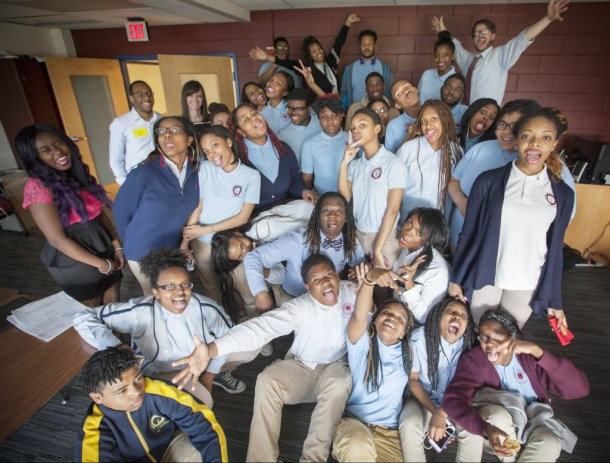 Teacher Bill Stevens shows off his signature arms-wide-open move in a group photo with students from the SEED Public Charter School following the in-school judging of National History Day projects.