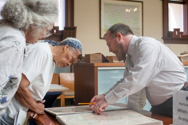 Matthew Gilmore helps participants locate where their buildings of interest using real estate atlases.