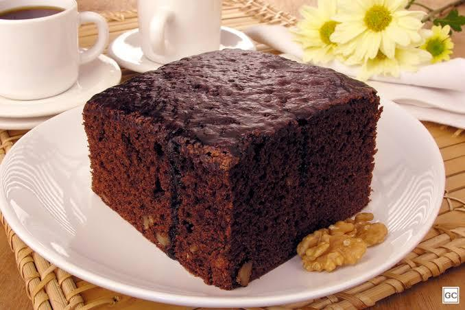 Um pedaço quadrado de bolo de chocolate tipo brownie, em um prato branco