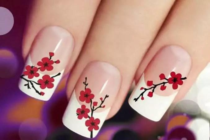 Unhas da mão com flores vermelhas e francesinha branca