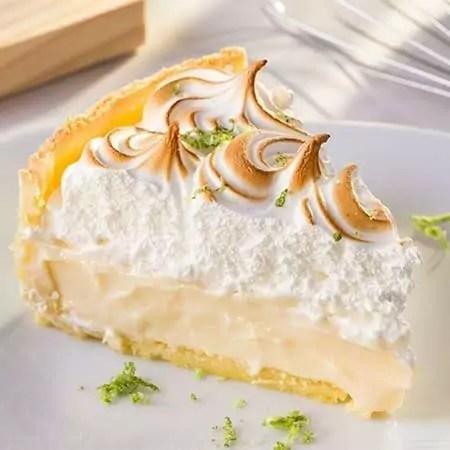Um pedaço triangular de torta de limão com a cobertura dourada - receitas de torta de limão