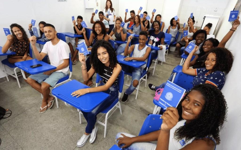 Sala de aula com estudantes sentados nas carteiras e com a com a carteira de trabalho na mão.