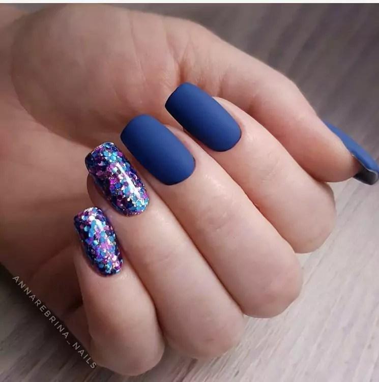 Unhas azuis com glitter colorido