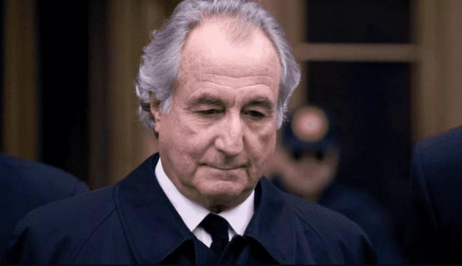 Homem idoso, branco, de cabeça baixa vestindo um terno preto.
