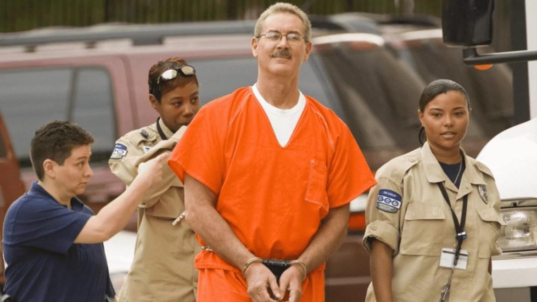 Ex-milionário sendo preso, vestindo uma roupa laranja, escoltado por policiais.