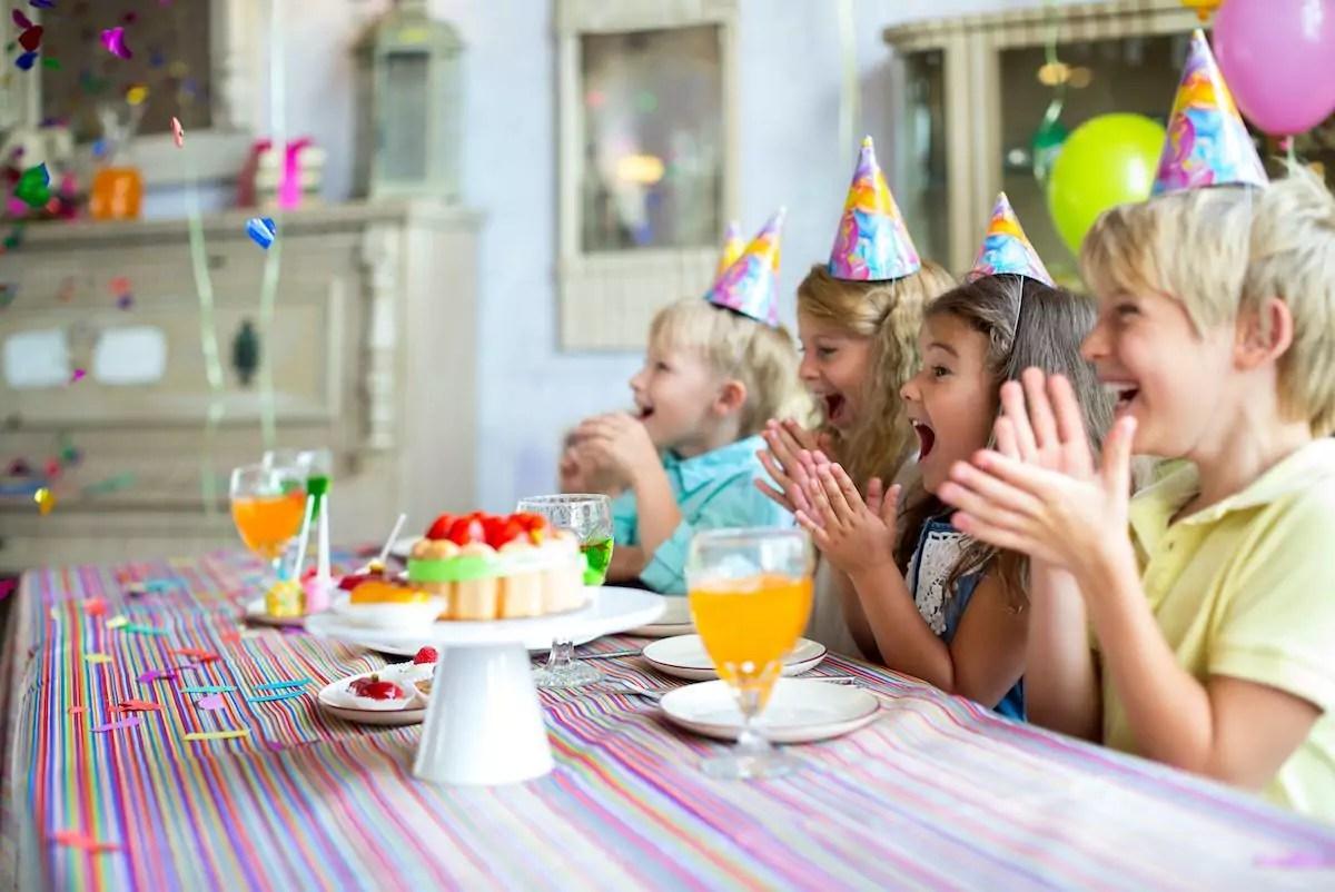 crianças em festa de aniverário cantando parabéns de forma bem alegra
