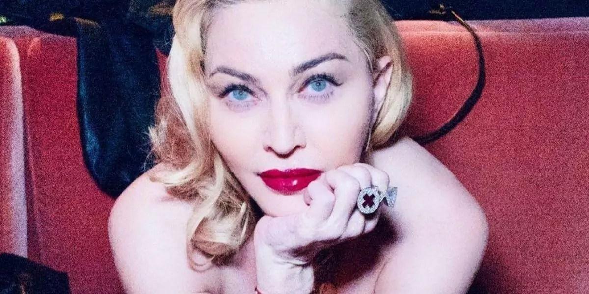 Madonna deitada olhando para frente com a mão no queixo