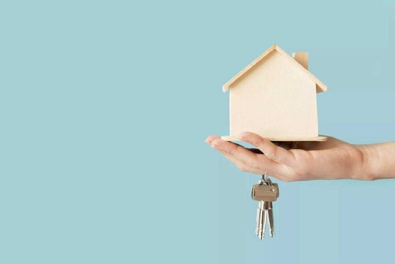 Mão segurando chave e casa de madeira