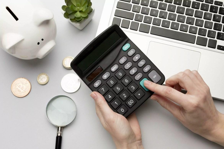 Reserva de emergência. Pessoa usando a calculadora, na cena há moedas, um cofrinho e um notebook.