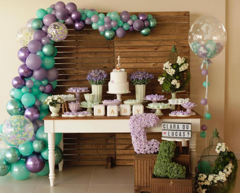 Decoração com mesa de bolo e balões lilás e verde para chá revelação