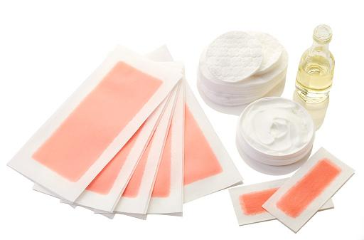 Pink waxing strips, cream and body oil isolated on white background depilação caseira