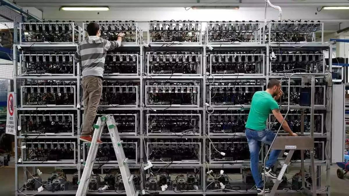 técnicos fazendo manutenção em uma mineradora industrial para minerar bitcoin