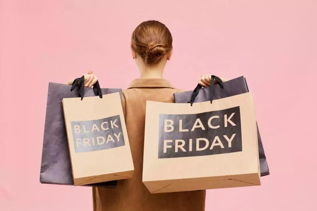 mulher de costas com sacolas escritas Black Friday