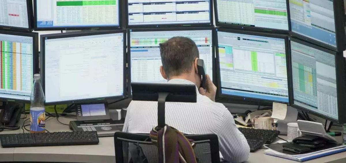 market maker sentado ao telefone em frente a várias telas de computador