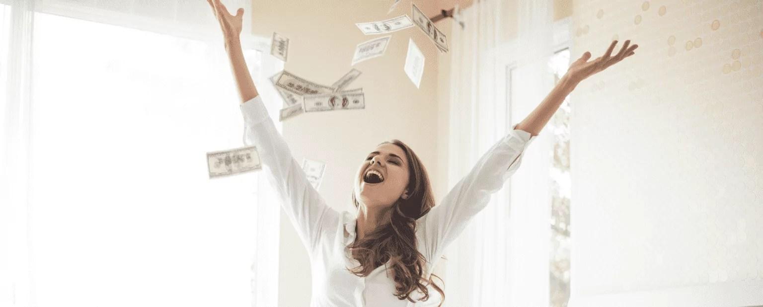 A imagem mostra uma mulher feliz jogando cédulas de dinheiro para o alto