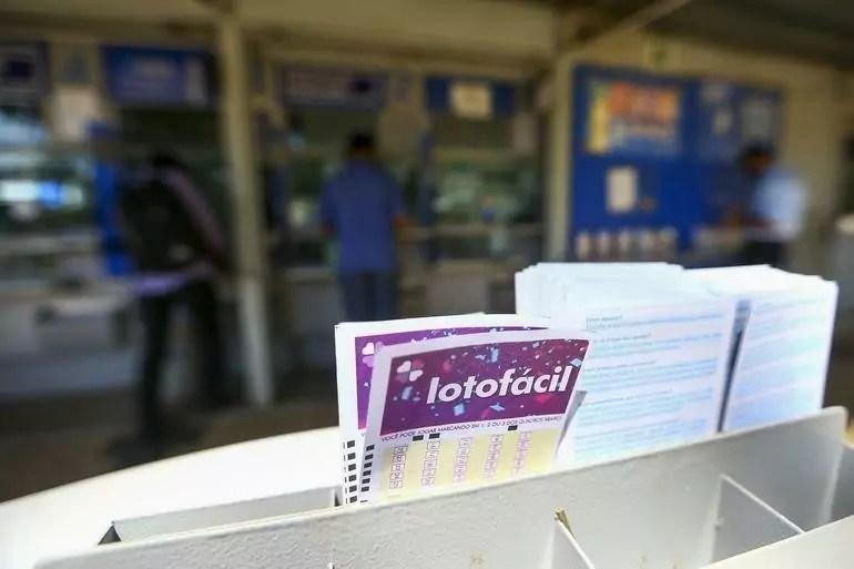 no primeiro plano, um bilhete da lotofácil e ao fundo uma lotérica descocada, resultado da lotofácil
