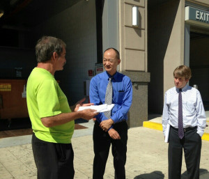 Ted Glick, left, speaks to FERC Chairman Norman Bay and an assistant.