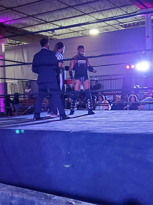 Man stands in wrestling ring preparing to wrestle