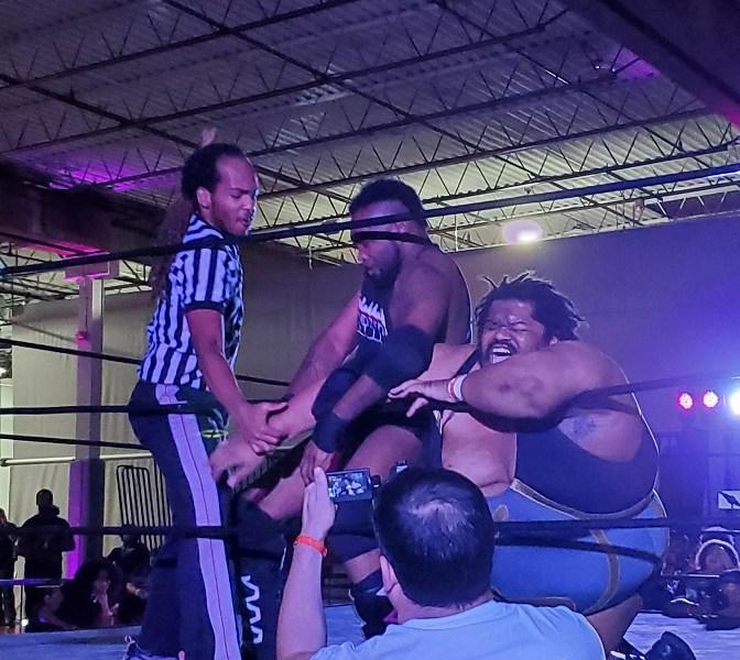 Wrestler attacks other wrestlers arm