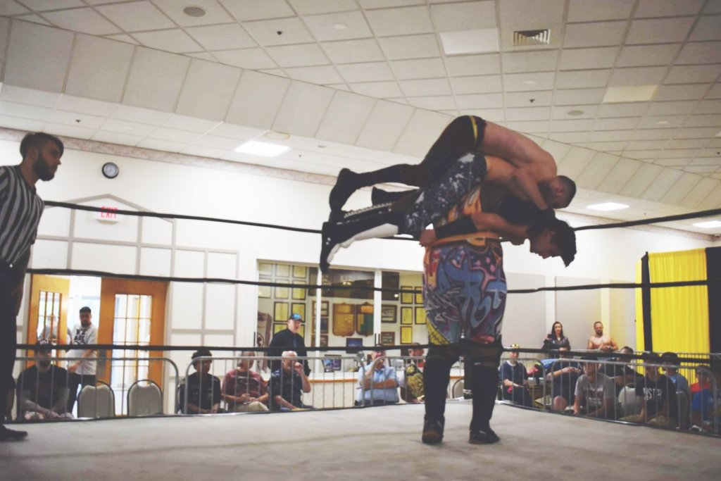 A man in a wrestling ring lifts three other wrestlers on his shoulders