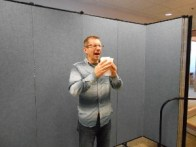 A man sneezing in front of a Screenflex Room Divider