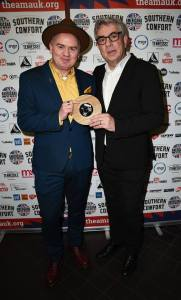 Dean Owens (in teal suit, hat and yellow shirt, being presented with Americanafest UK Song of the Year Award 2019 by Graham Gouldman (10CC)