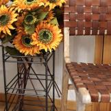 Hand woven Leather Chair and metal umbrella stand with sunflowers