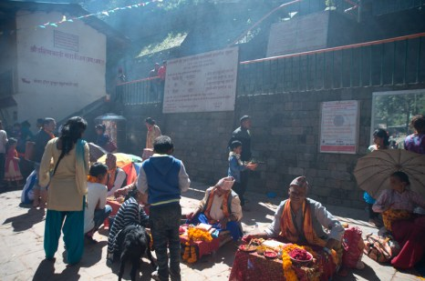 In front of the temple entrance, holy people give red tika for blessings