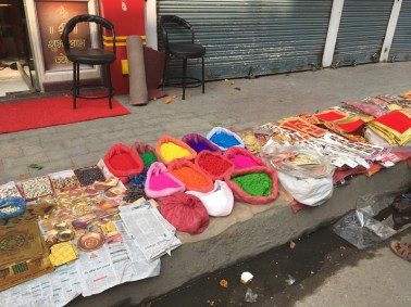 Colorful dye powder and red paper to be used in the festival.