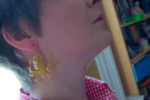 golden spider earring on ear