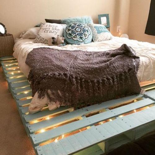 Muebles con palets originales como esta base de cama pintada de azul con guirnalda de luces interior.