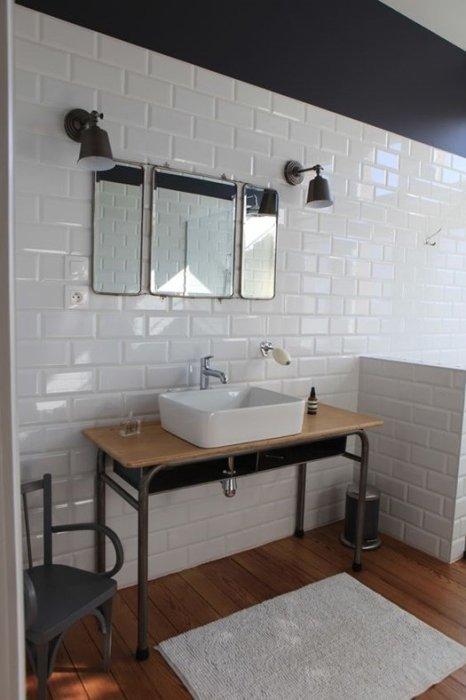 Cuarto de baño de estilo industrial con mueble de lavabo tipo pupitre.