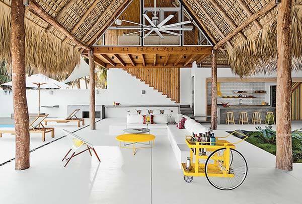 Cemento pulido, color mostaza y naturaleza para una casa en la playa