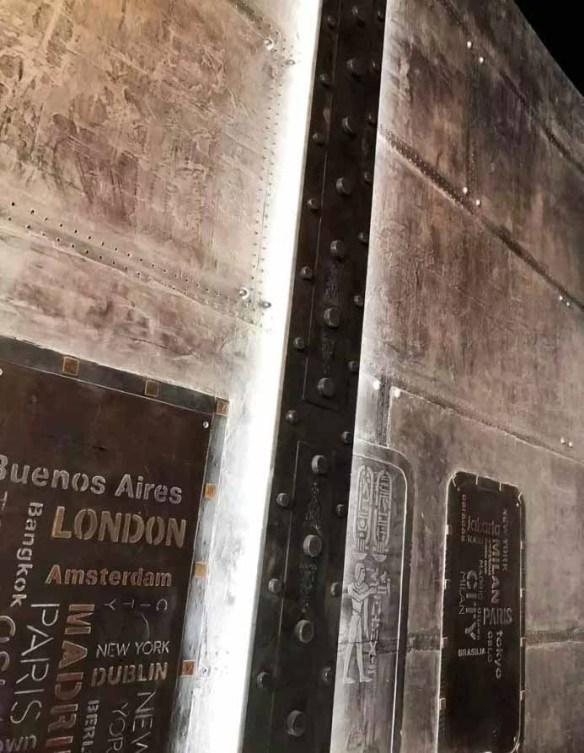 décoration hôtel style industriel avec IPN style Eiffel et enseigne publicitaire sur murs métal