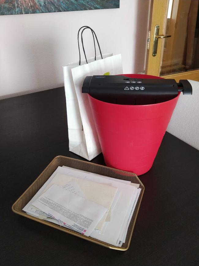 bolsa para reciclar papel y una trituradora para despejar la pila de papeles