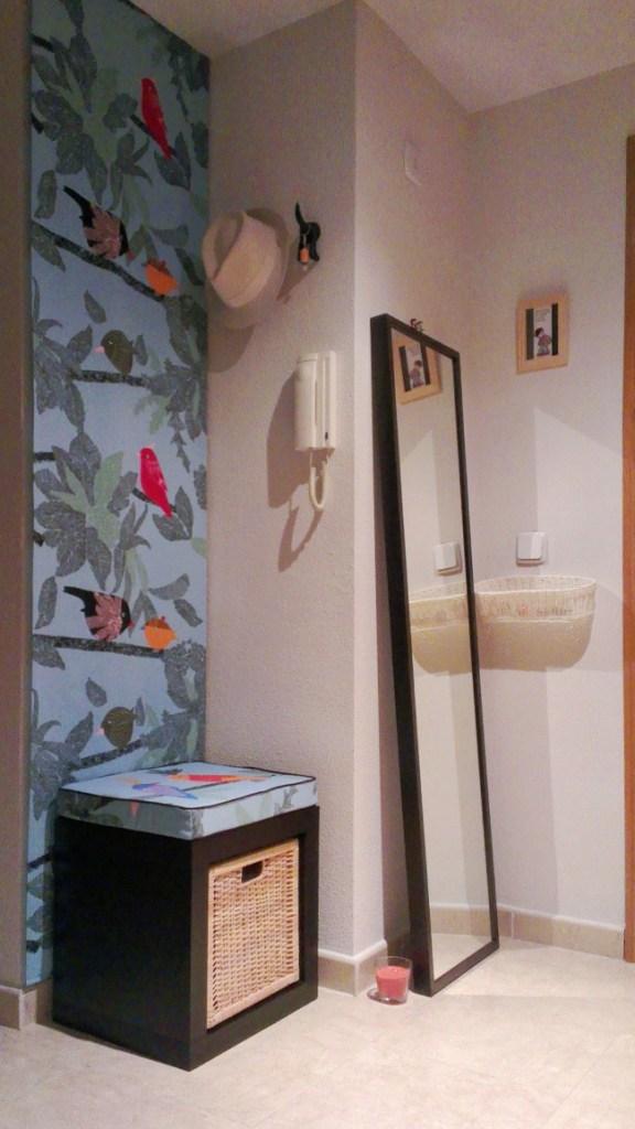 Banco con almacenaje, ganchos, espejo y cesto para sacar partido a un recibidor pequeño. El tapiz, la lámina y la vela le dan un toque de personalidad.