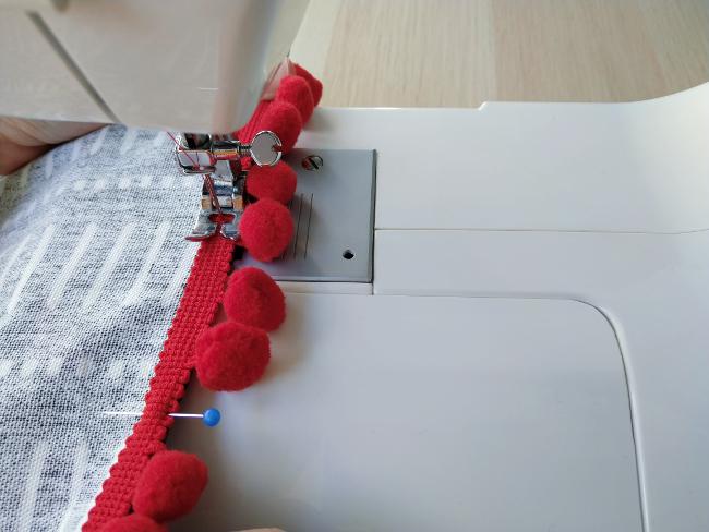 cosiendo a máquina la tira sobre la cortina