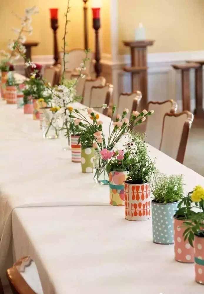 A mesa da festa pode ficar mais bonita e divertida com os arranjos feitos em latinhas de alumínio; repare que elas foram revestidas com papel contact